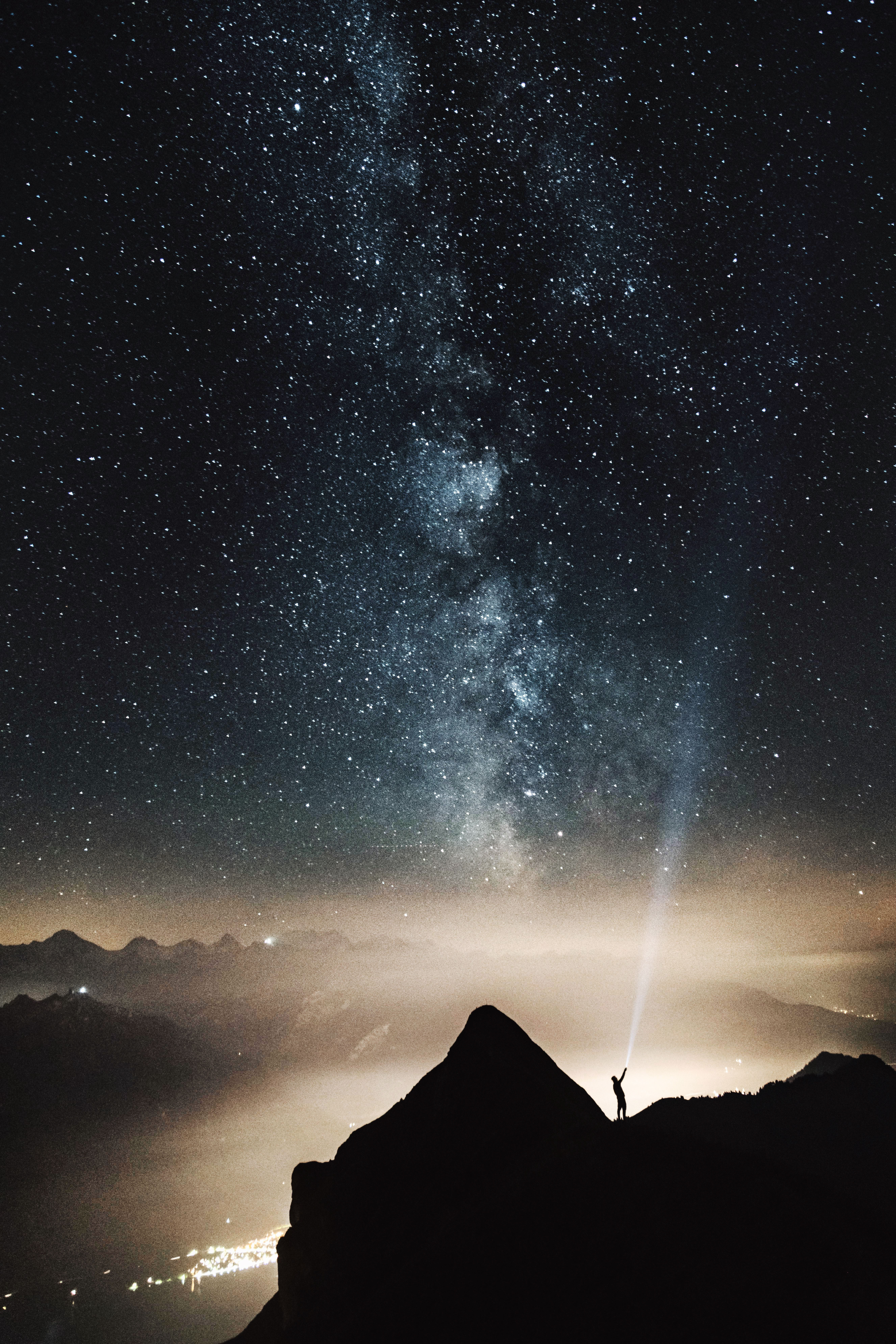 silhouette of person on top of mountain pointing flashlight on sky filled with stars at night time