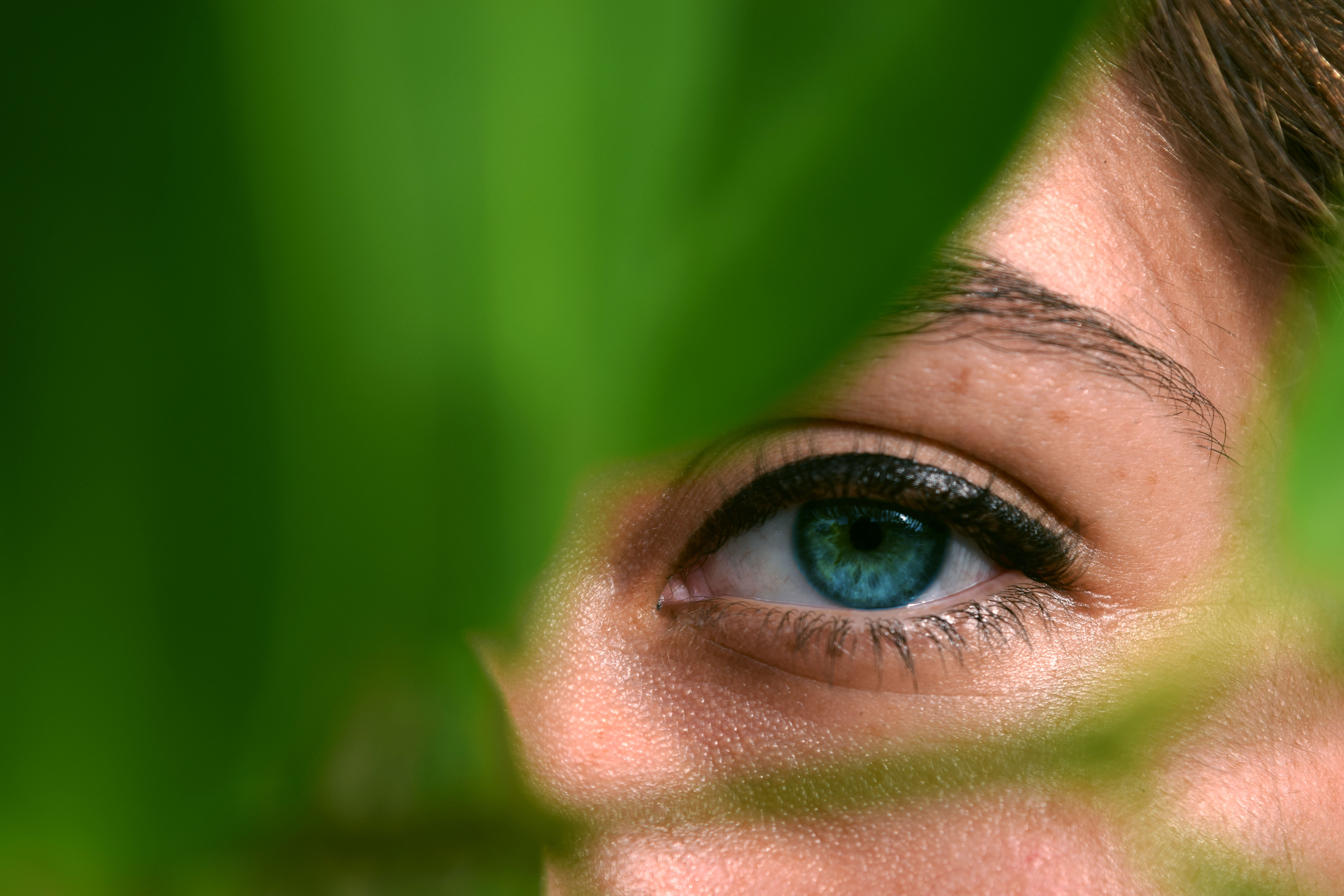 person watching through green leaf